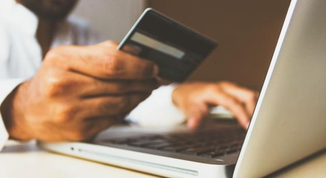 Image shows hands holding a credit card in front of a laptop computer